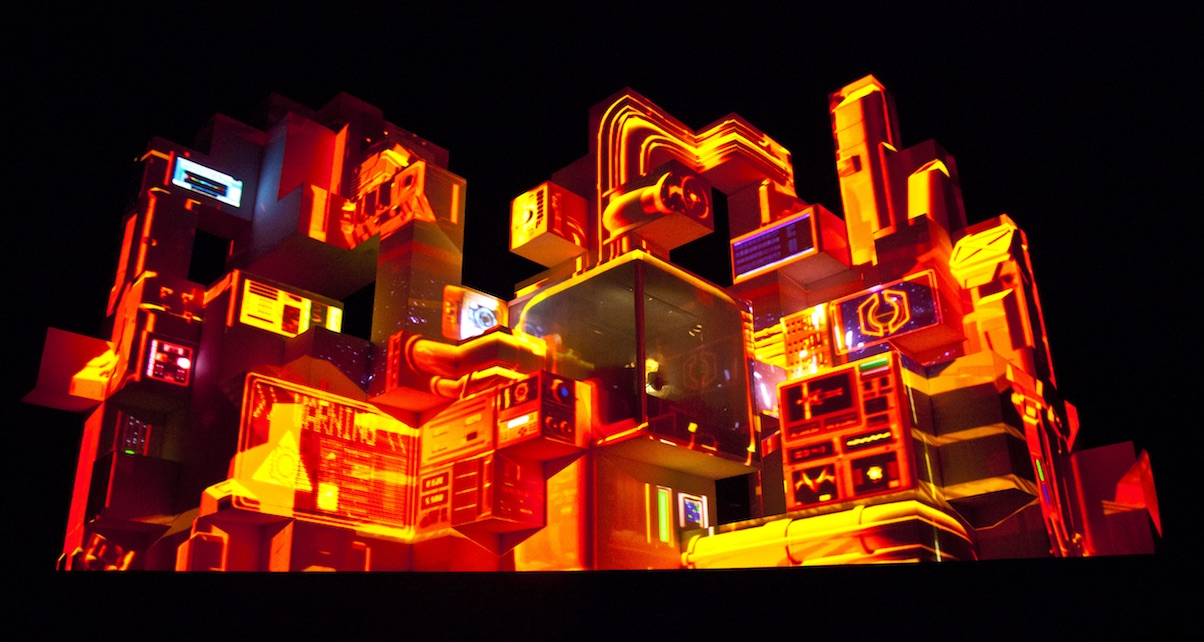 Amin Tobin incorporates the use of new video mapping techniques that are projected onto a large cubic structure from which he performs.