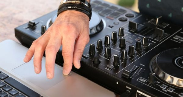 Controller DJ searches for music on laptop
