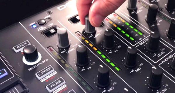 DJ adjusts volume on mixer