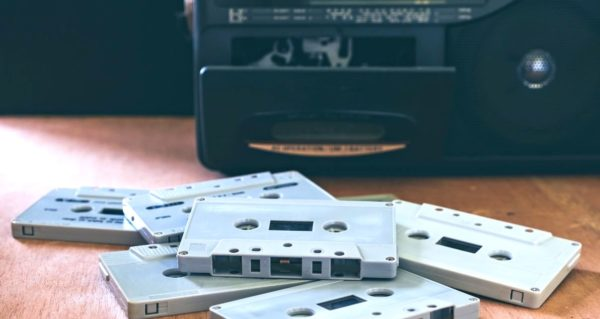 Pile of cassette tapes in front of a player